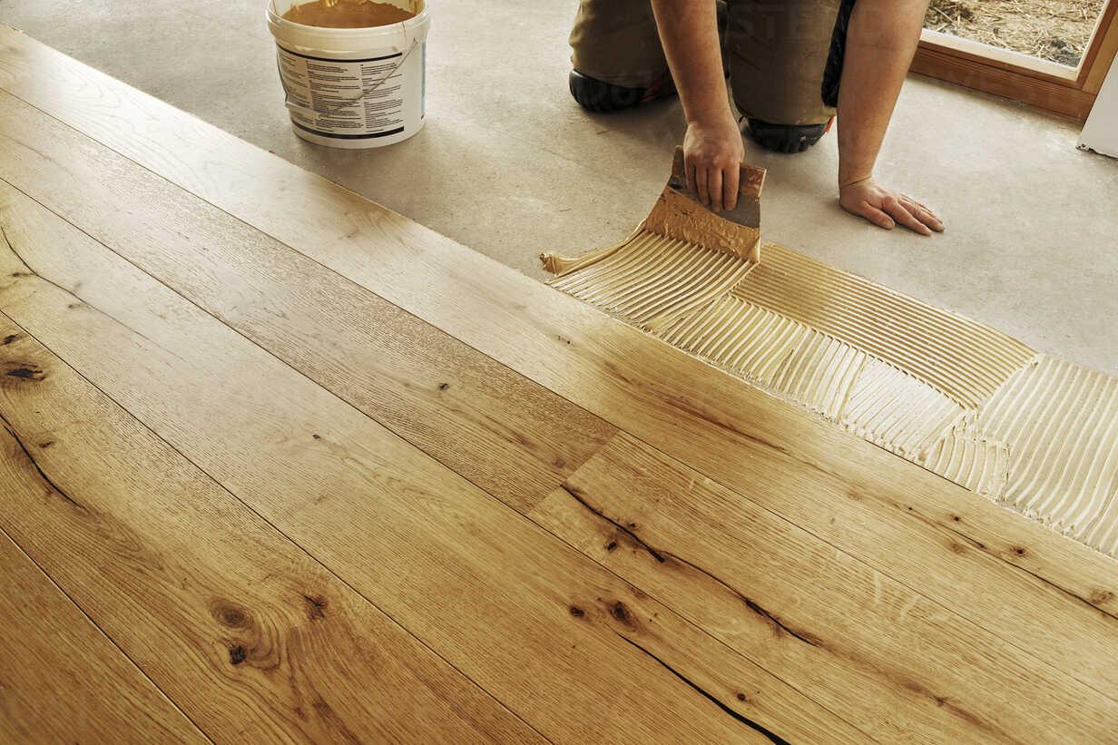 Man laying finished oak parquet flooring, close-up - BIF000298 - Ingo Bartussek/Westend61