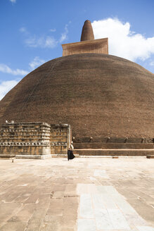 Sri Lanka, North Central Province, monk in front of a stupa near Anuradhapura - DR000433