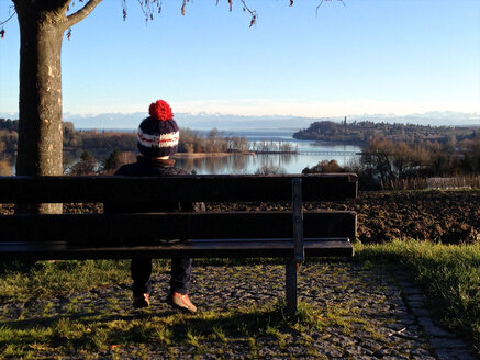 Boy on bench looking to Mainau Island, Germany, Baden-Wuerttemberg, Constance, Lake Constance - JEDF000085