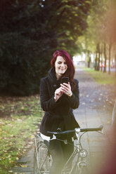 Portrait of smiling woman using smartphone - FEXF000069