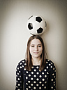 Young woman with a football on her head - JATF000594