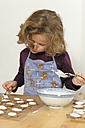 Little girl spreading cinnamon stars with  sugar icing - LAF000443