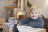 Smiling blond boy in a cafe, portrait - MJF000630