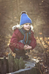 Boy crouching on tree stump - MJF000696