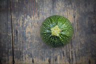 Round courgette on dark wooden table, elevated view - LVF000484