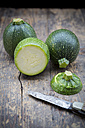 Sliced and whole round courgettes and a pocket knife on dark wooden table - LVF000478