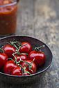 Metal bowl of cherry tomatoes, preserving jar with tomato sauce on wooden table - LVF000472