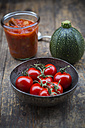 Metal bowl of cherry tomatoes, preserving jar with tomato sauce and zucchini on wooden table - LVF000470