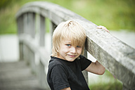 Portrait of little boy standing on wooden boardwalk - PAF000269
