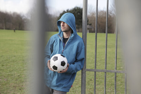 Young man with football leaning at goalpost - JATF000610