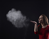 Young woman blowing dust - BFRF000326