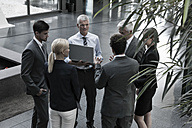 Group of businesspeople with laptop talking in lobby - CHAF000035