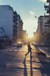 Italy, Sicily, Palermo, Street view at sunset with man walking his dog - MF000810