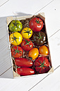 Wooden box with different tomatoes on wooden table - CSF020738