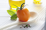 Orange tomato on wooden spoon, olive oil, basil and peppercorns on wooden table - CSF020717
