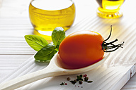 Orange tomato on wooden spoon, olive oil, basil and peppercorns on wooden table - CSF020680