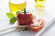 Tomato Red Zebra on wooden spoon, olive oil, basil and peppercorns on wooden table - CSF020677