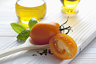 Orange tomato on wooden spoon, olive oil, basil and peppercorns on wooden table - CSF020674