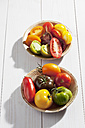 Different sliced tomatoes in bowls on wooden table - CSF020671