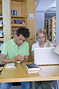 Germany, Baden-Wuertemberg, two students with laptop learning in a library - CHAF000102