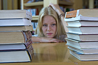 Germany, Baden-Wuertemberg, stressed young female student with stack of books in a library - CHAF000106