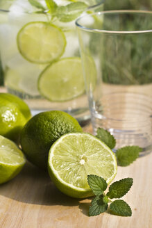 Sliced and whole limes and glass on wooden table - YFF000012
