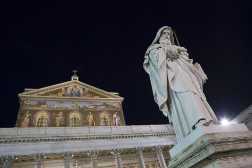 Italy, Rome, view to gable of Papal Basilica of St Paul Outside the Walls by night, in front statue of St Paul - DIS000432
