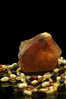 Raw amber and amber necklace in front of black background - JAWF000002
