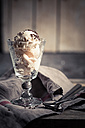 Glass of vanilla icecream with chocolate granules, spoons and kitchen towel on wood - SBDF000509