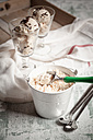 Two glasses of vanilla icecream with chocolate granules, zinc bucket of vanilla icecream, ice cream scoop, spoons and kitchen towel on wood - SBDF000514
