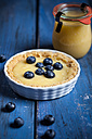 Lemon tart decorated with blueberries and glass of lemon curd on blue wooden table - SBDF000493