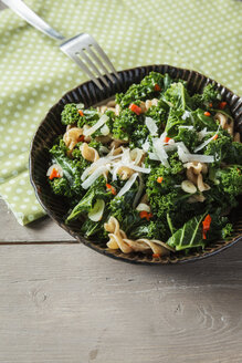 Bowl of spelt whole-grain noodles, curly kale, red chili pepper, garlic, onion and parmesan on wooden table - EVGF000343