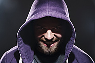Portrait of man with hooded jacket in front of black background - PD000619