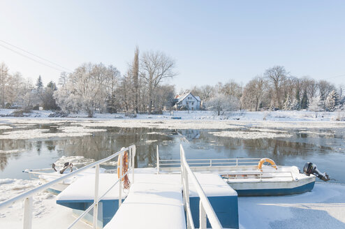Germany, view to jetty and boat on frozen lake - MJ000782