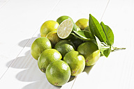 Limes and leaves on wooden table - CSF020743