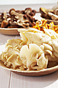 Fresh mushrooms, Golden Oyster Mushroom (Pleurotus citrinopileatus), Chanterelles (Cantharellus cibarius), Agrocybe aegerita and Ceps (Boletus edulis) in bowls on wooden table - CSF020746