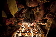 India, Uttar Pradesh, Varanasi, Maha Shivaratri, a family lighting oil lamps - JBA000046