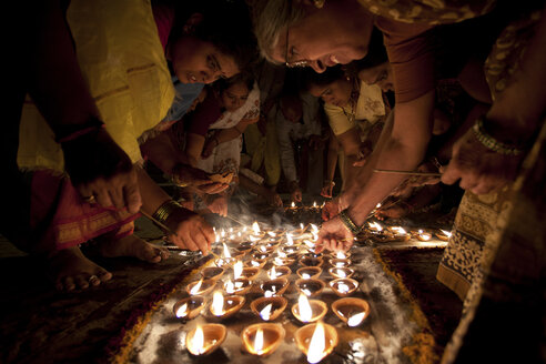 India, Uttar Pradesh, Varanasi, Maha Shivaratri, a family lighting oil lamps - JBA000046