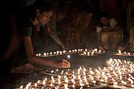 India, Uttar Pradesh, Varanasi, Maha Shivaratri, a woman lighting oil lamp - JBA000048