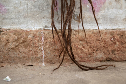 India, Uttar Pradesh, Varanasi, hair of Sadhu in front of wall - JBA000062