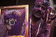 India, Uttar Pradesh, Mathura, man with picture of Krishna at Holi, spring festival, festival of colours - JBA000021