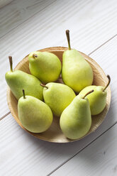 Palmleaf plate of pears (Pyrus) on white wooden table - CSF020787