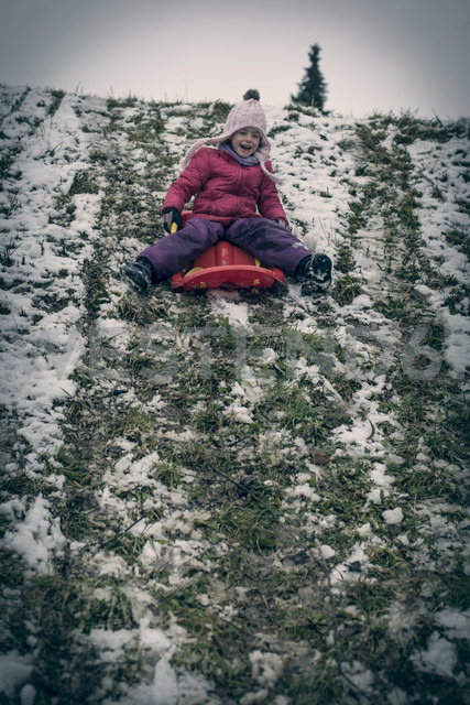 Germany, Bavaria, Landshut, laughing  little girl tobogganing - SARF000222