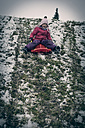 Germany, Bavaria, Landshut, laughing  little girl tobogganing - SARF000222