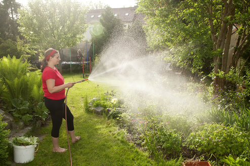 Woman in garden watering plants - BFRF000339