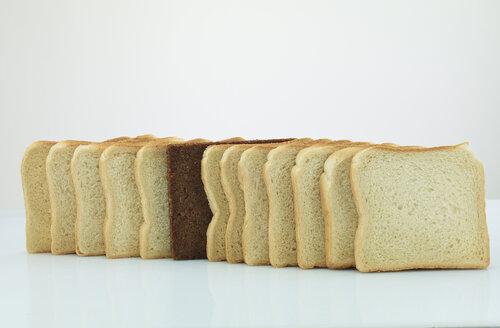 Single slice of black bread in a row of toast bread - AKF000316