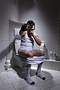 Germany, Man sitting on toilet, using smart phone - MAEF007691