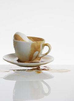 White coffee splashing out of coffee cup in front of white background - AKF000300