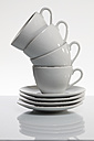 Stack of white coffee cups in front of white background - AKF000304