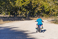 USA, Texas, Little boy riding bike with stabilisers - ABAF001195